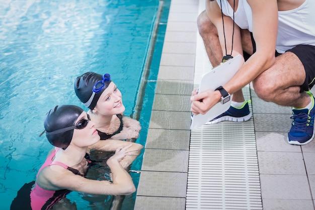 レジャーセンターでクリップボードを見て笑顔の水泳選手