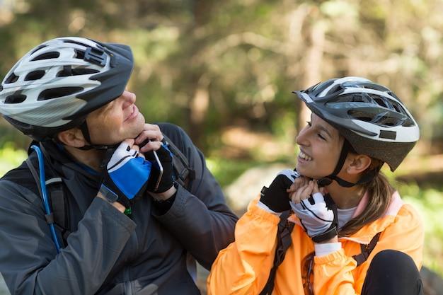 森で自転車のヘルメットを身に着けているバイカーカップル