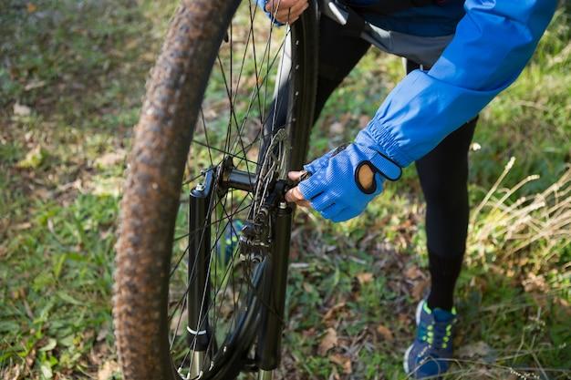 彼の自転車の鎖を修正する男性男性マウンテンバイクのクローズアップ