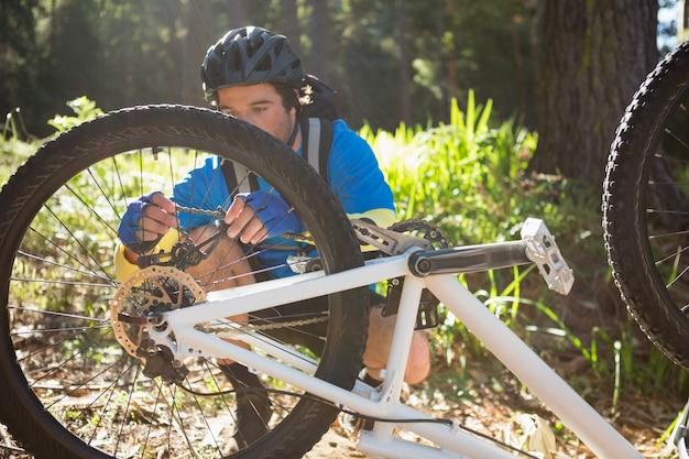 男性男性マウンテンバイクの彼の自転車のチェーンを修正