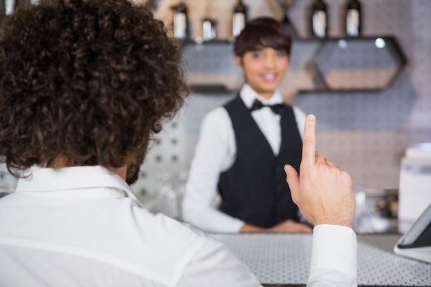 バーカウンターでドリンクを注文する男性