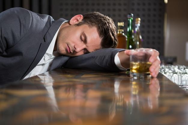 ウイスキーのグラスをカウンターに横になっている酔っぱらい