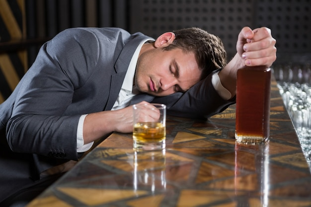 ウイスキーのボトルとカウンターの上に横たわる酔っぱらい