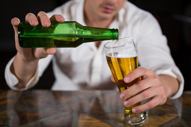 グラスにビールを注ぐ男