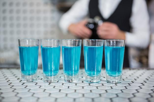 バーのカウンターでブルーラグーンドリンクのグラス