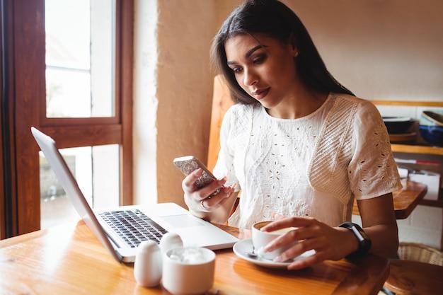 Красивая женщина, с помощью мобильного телефона, имея чашку кофе
