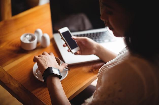 Женщина с помощью мобильного телефона, имея чашку кофе