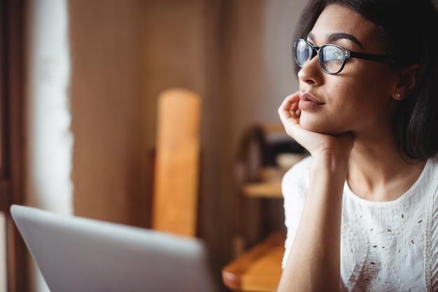 Вдумчивый женщина, сидящая с ноутбуком