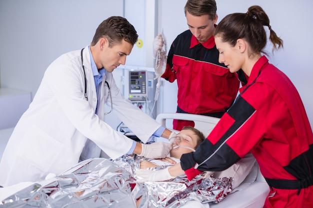 緊急治療室で患者を診察する医師と救急救命士