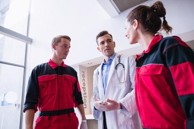 廊下で救急救命士に話している医者