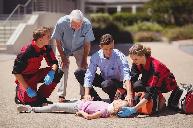 負傷した女の子を調べる救急隊員