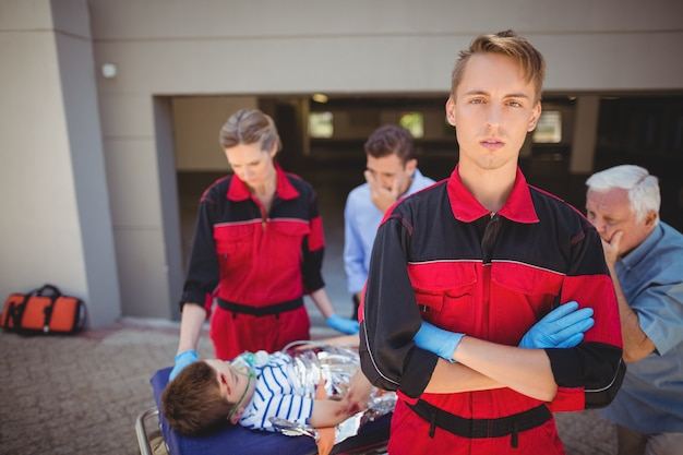 負傷した少年を調べる救急隊員