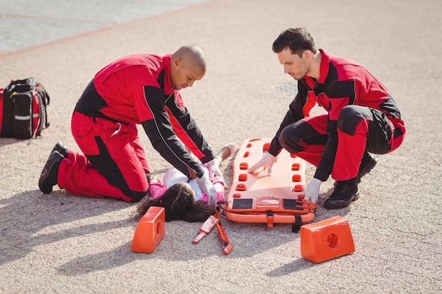 負傷した女の子を背板に置く救急隊員