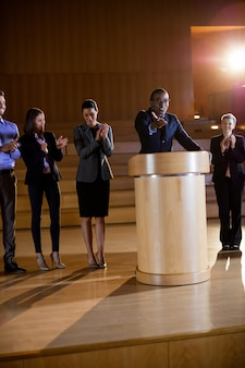 Коллеги аплодируют докладчику после презентации конференции