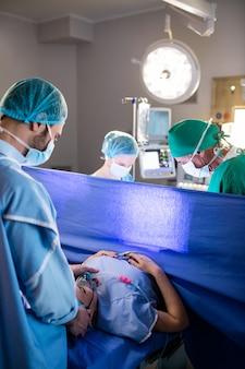 出産中に妊娠中の女性を調べる医師