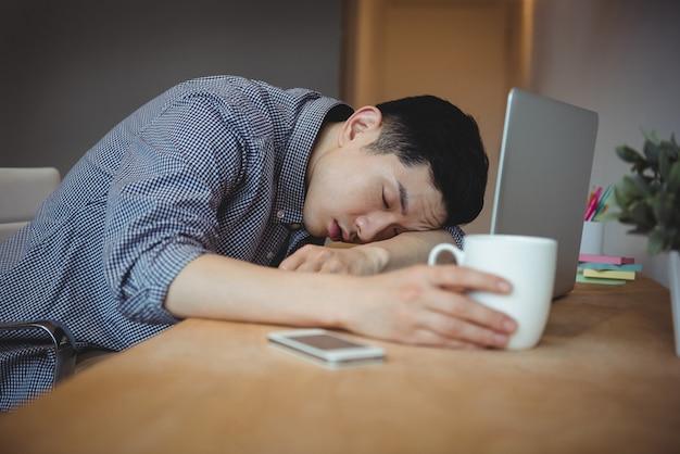 彼の机で寝ているビジネスエグゼクティブ