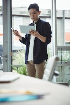 Руководитель бизнеса используя мобильный телефон и цифровую таблетку