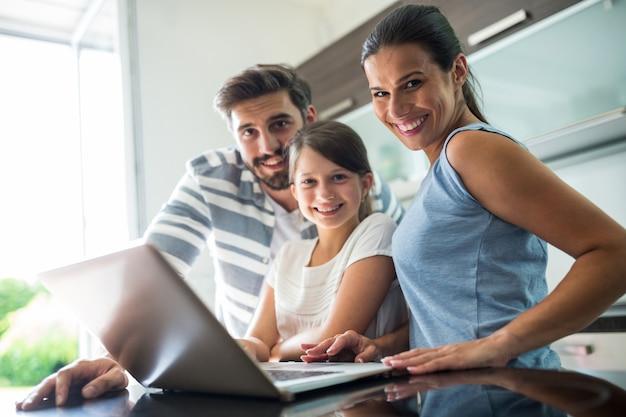 リビングルームでラップトップを使用して幸せな家族