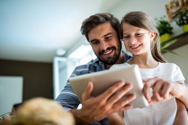 父と娘のリビングルームでデジタルタブレットを使用して