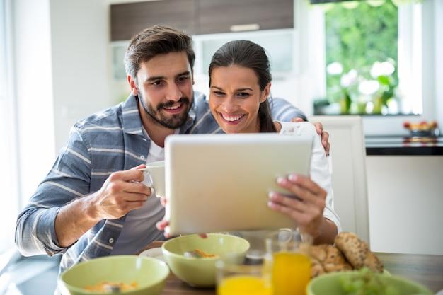 朝食をとりながらデジタルタブレットを使用してカップル