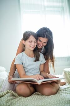 母と娘のベッドで本を読んで