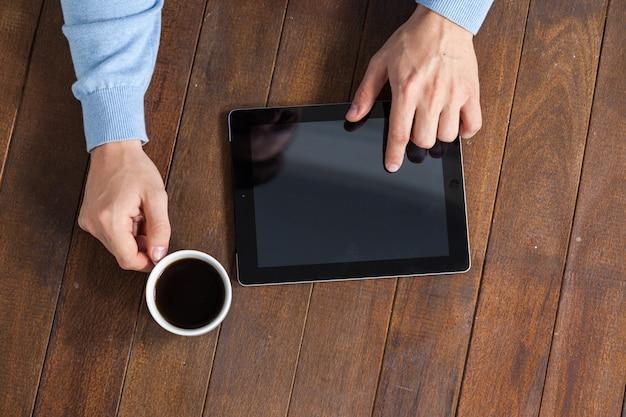 一杯のコーヒーを持ちながらデジタルタブレットを使用している人