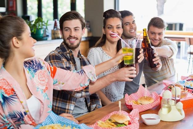 Веселые друзья наслаждаются пивом с едой в ресторане