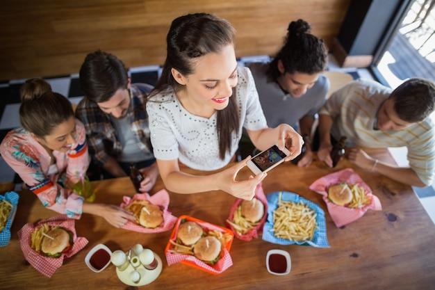 Женщина с друзьями фотографировать еду в ресторане