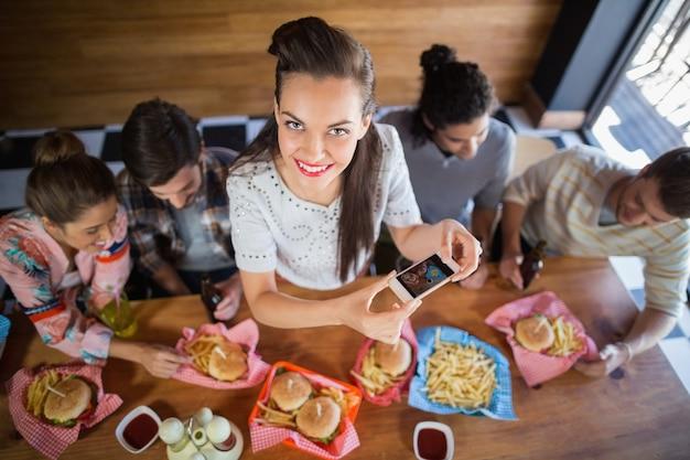 Молодая женщина с друзьями фотографировать еду в ресторане