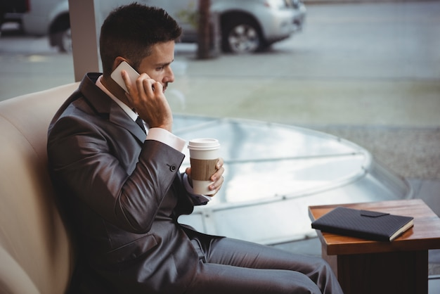 Бизнесмен держит кофе во время разговора по мобильному телефону
