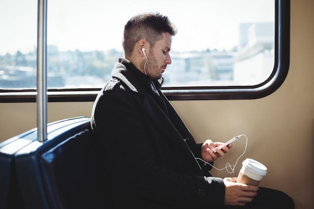 使い捨てのコーヒーカップを押しながら携帯電話で音楽を聞くビジネスマン