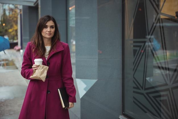 Предприниматель, держа одноразовые чашки кофе, посылки и дневник