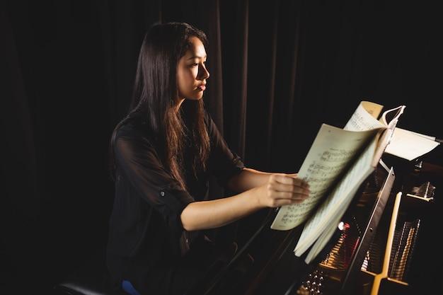 Студентка смотрит на ноты во время игры на пианино