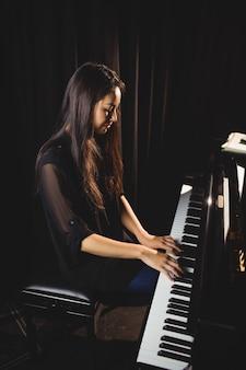 音楽スタジオでピアノを弾く女性