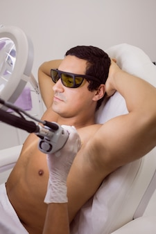 男性患者の皮膚にレーザー脱毛を行う医師