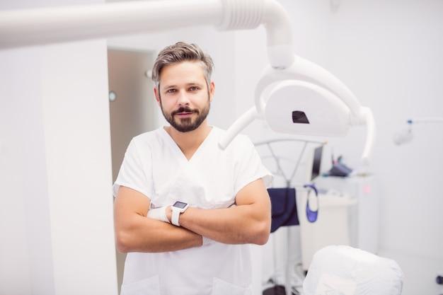 Стоматолог, стоя со скрещенными руками