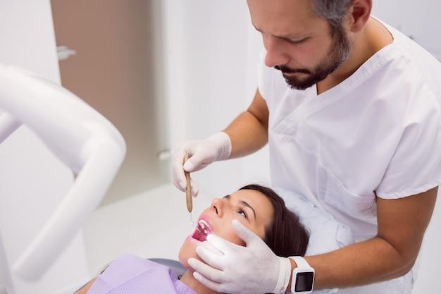 Стоматолог, осмотр зубов пациентки с зеркалом рта