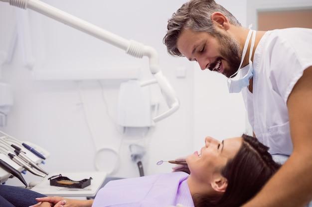 Стоматолог, улыбаясь при осмотре пациента