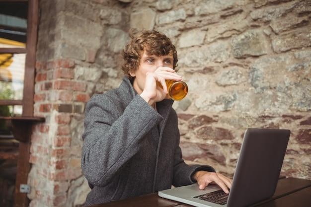 Человек, имеющий пиво при использовании ноутбука