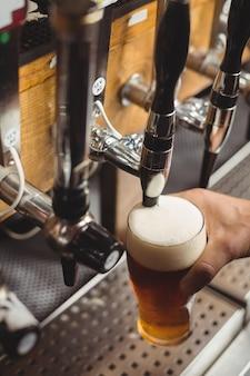 バーポンプからのバーテンダーフィリングビールのクローズアップ