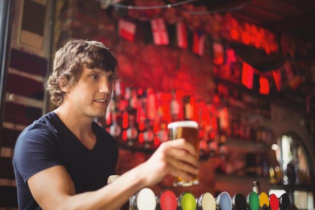 顧客にビールのグラスを提供するバーテンダー