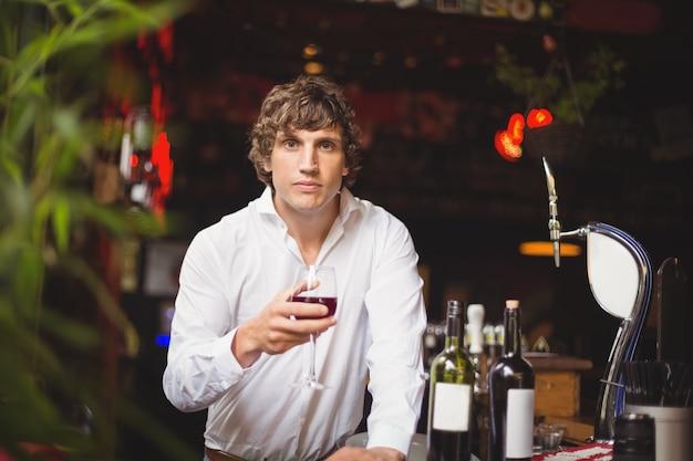 赤ワインのガラスを保持している柔らかいバーの肖像画