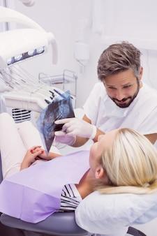 Стоматолог показывает рентгеновский снимок пациенту