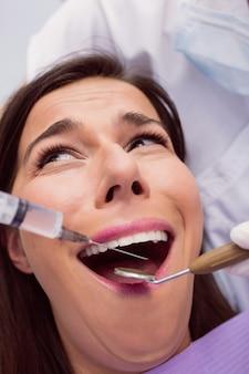 怖がっている女性患者の口に麻酔薬を注入する歯科医
