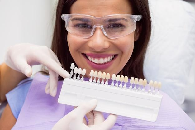 歯科医が歯の色合いを持つ女性患者を調べる