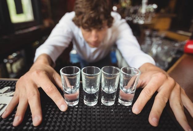 バーカウンターでアルコール飲料のショットグラスを準備して裏打ちするバーテンダー