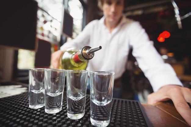Крупным планом текилы бармена наливание в рюмки