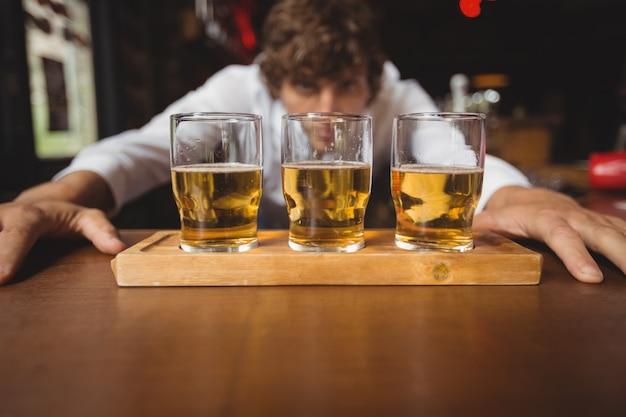 バーカウンターにウイスキーショットグラスを並べるバーテンダー