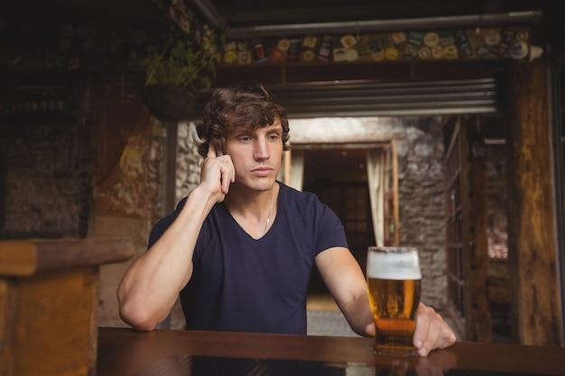 Человек разговаривает по мобильному телефону в баре