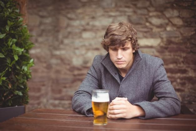 Человек сидит в баре с бокалом пива на столе